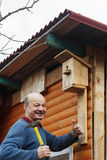 Bald senior with a mustache attaches birdhouse to the barn Stock Photography