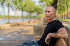 Bald senior tourist man with hand tattoos thinking and sitting o. N the wooden bench at peaceful park in Bangkok Thailand stock images