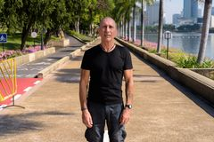 Bald senior tourist man standing at peaceful park in Bangkok Tha. Iland stock photo