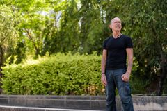 Bald senior tourist man standing and thinking while looking up a. T peaceful park in Bangkok Thailand stock photography