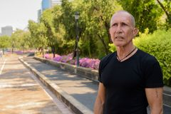 Bald senior tourist man thinking on the side of the street at pe. Aceful park in Bangkok Thailand royalty free stock image