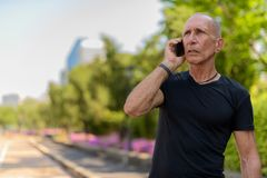 Bald senior tourist man thinking while talking on mobile phone a. Gainst view of the street at peaceful park in Bangkok Thailand stock photo