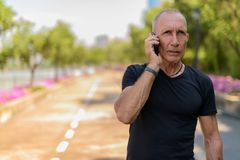 Bald senior tourist man thinking while talking on mobile phone o. N the side of the street at peaceful park in Bangkok Thailand stock images