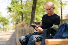 Bald senior tourist man using digital tablet with eyeglasses whi. Le sitting on the wooden bench at peaceful park in Bangkok Thailand royalty free stock photo