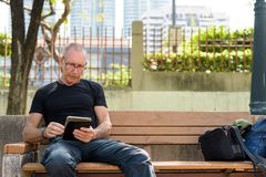 Bald senior tourist man using digital tablet while sitting on th. E wooden bench against view of the city at peaceful park in Bangkok Thailand stock photo