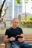 Bald senior tourist man using digital tablet while sitting on th. E wooden bench at peaceful park in Bangkok Thailand royalty free stock images