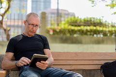 Bald senior tourist man using digital tablet while wearing eyegl. Asses and sitting on the wooden bench at peaceful park stock photos