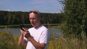 Bald smiling man waving while talking on video chat with phone near lake outside stock video footage