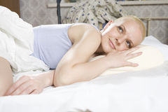 Bald smiling woman lying in bed Royalty Free Stock Images