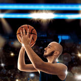 Bald sportsman playing basketball and thorws a ball Royalty Free Stock Images