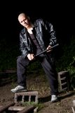 Bald thug armed with baton outdoors at night. Bald athletic thug in black leather jacket and sportive costume armed with police baton Royalty Free Stock Photography