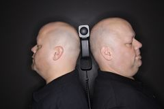 Bald twin men with telephone. Royalty Free Stock Image