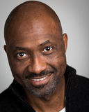 Bald Unshaven Black Man In His Forties. Portrait of a bald unshaven black man with a mustache wearing a black cardigan isolated against a grey background Stock Photos