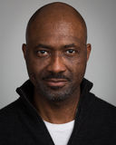 Bald Unshaven Black Man In His Forties. Portrait of a bald unshaven black man with a mustache wearing a black cardigan isolated against a grey background Royalty Free Stock Image