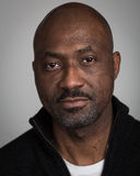 Bald Unshaven Black Man In His Forties. Portrait of a bald unshaven black man with a mustache wearing a black cardigan isolated against a grey background Royalty Free Stock Images