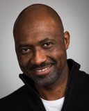 Bald Unshaven Black Man In His Forties. Portrait of a bald unshaven black man with a mustache wearing a black cardigan isolated against a grey background Stock Images