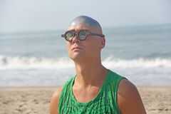 A bald and unusual young man, a freak, with a shiny bald head an. D round wooden glasses on the background of the beach and the sea. Humor and eccentricity Stock Photo