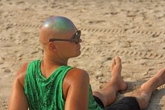 A bald and unusual young man, a freak, with a shiny bald head an. D round wooden glasses on the background of the beach and the sea. Humor and eccentricity Stock Photography