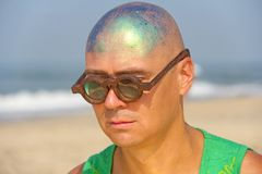 A bald and unusual young man, a freak, with a shiny bald head an. D round wooden glasses on the background of the beach and the sea. Humor and eccentricity Stock Images