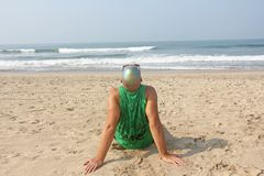 A bald and unusual young man, a freak, with a shiny bald head and round wooden glasses on the background of the beach and the sea. Humor and eccentricity stock image