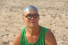 A bald and unusual young man, a freak, with a shiny bald head and round wooden glasses on the background of the beach and the sea. Humor and eccentricity stock photography