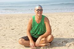 A bald and unusual young man, a freak, with a shiny bald head and round wooden glasses on the background of the beach and the sea. Humor and eccentricity royalty free stock photos