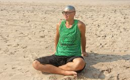 A bald and unusual young man, a freak, with a shiny bald head and round wooden glasses on the background of the beach and the sea. Humor and eccentricity royalty free stock images