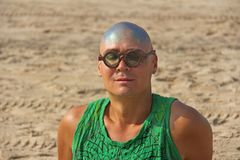A bald and unusual young man, a freak, with a shiny bald head and round wooden glasses on the background of the beach and the sea. Humor and eccentricity royalty free stock photography