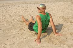 A bald and unusual young man, a freak, with a shiny bald head and round wooden glasses on the background of the beach and the sea. Humor and eccentricity stock photo