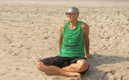 A bald and unusual young man, a freak, with a shiny bald head and round wooden glasses on the background of the beach and the sea. Humor and eccentricity royalty free stock photo
