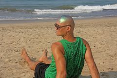 A bald and unusual young man, a freak, with a shiny bald head and round wooden glasses on the background of the beach and the sea. Humor and eccentricity royalty free stock image