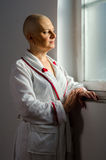 Bald woman with cancer in the hospital. Bald woman suffering from cancer looking throught the hospital window Royalty Free Stock Photography
