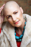 Bald woman in fur coat. Beautiful happy bald woman in fake fur coat and turquoise necklace Royalty Free Stock Photo