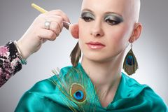 Bald woman getting makeup. Hand working on makeup of hairless woman Royalty Free Stock Photo