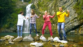 Bald woman her children and husband are dancing against the backdrop of a waterfall, looking at the camera. stock footage