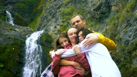 A bald woman, her children and her husband are hugging on the background of a waterfall, looking at the camera. stock video