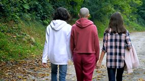 Bald woman, mother and her teenage children walk together in a park or forest stock video footage