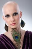 Bald woman with peacock plume. Portrait of beautiful hairless woman using peacock plumes as accessory Royalty Free Stock Photo