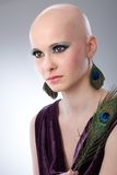 Bald woman with peacock plume. Portrait of beautiful hairless woman using peacock plumes as accessory Stock Photo
