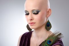 Bald woman with peacock plume. Portrait of beautiful hairless woman using peacock plumes as accessory Royalty Free Stock Images