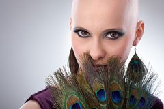Bald woman with peacock plumes. Portrait of beautiful hairless woman using peacock plumes as accessory Stock Photography
