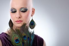 Bald woman with peacock plumes. Portrait of beautiful hairless woman using peacock plumes as accessory Royalty Free Stock Photos