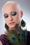 Bald woman with peacock plumes. Portrait of beautiful hairless woman using peacock plumes as accessory Stock Photo