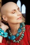 Bald woman in red. Beautiful happy bald woman in turquoise necklace enjoying the sunlight -  shot in natural light Stock Image