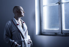 Bald woman suffering from cancer in hospital. Bald woman suffering from cancer looking throught the hospital window Royalty Free Stock Images