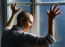 Bald woman suffering from cancer leaning on the hospital window.  Stock Photography