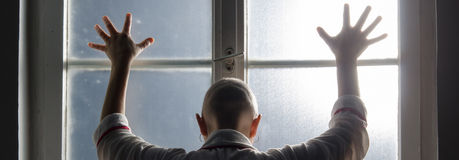 Bald woman suffering from cancer leaning on the hospital window.  Stock Photos