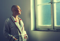 Bald woman suffering from cancer looking throught the hospital w Royalty Free Stock Image