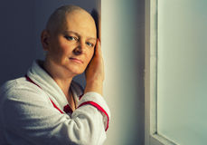 Bald woman suffering from cancer. Standing in front of the hospital window Stock Photo