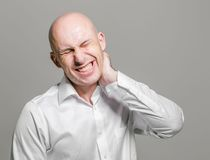 Bald young man portrait with neck pain Royalty Free Stock Image